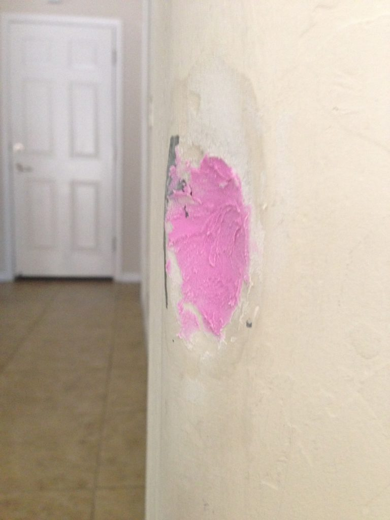 dented rounded drywall corner with thin layer of pink spackle applied