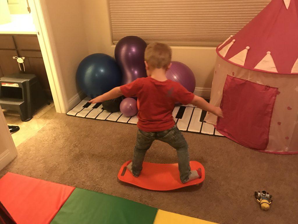 hyperactive son balancing on yoga balance board